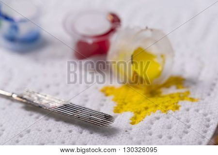 Closeup detail of colorful inks poured into small cups isolated on white background