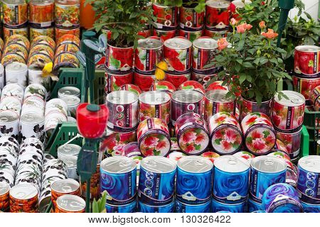 Amsterdam, Netherlands - March 31, 2016: Flower multi-colored cans with roses souvenirs for sale in Amsterdam, Netherlands