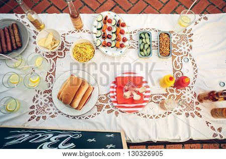 View from above of table with delicious food and drinks on tablecloth in a outdoors summer party