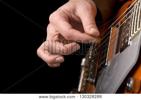 Horizontal close up of a hand playing an orange electrical guitar with shallow depth of field on dark background