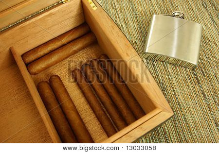 Cigars in open humidor. Hip-flask.