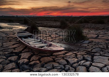 Wooden boat on drought land with sunset