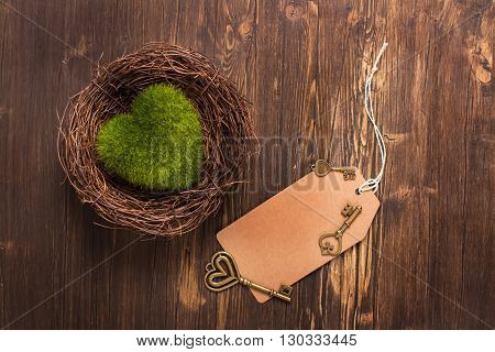 Green moss heart in a nest, keys and paper tag over wooden background. Toned image
