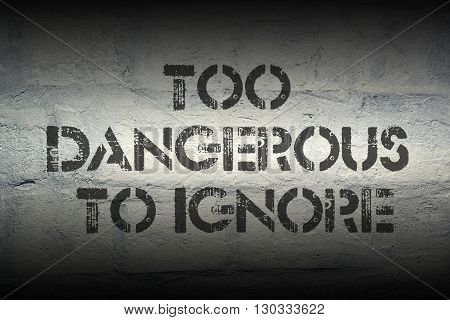 too dangerous to ignore stencil print on the grunge white brick wall