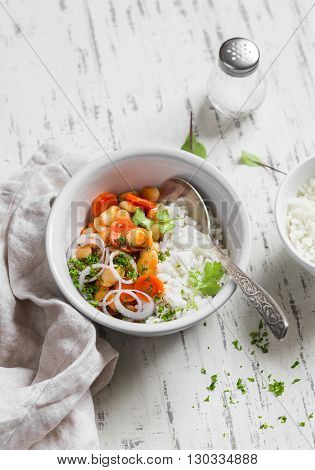 Rice with beans in tomato sauce on a light wooden background. Delicious healthy vegetarian food