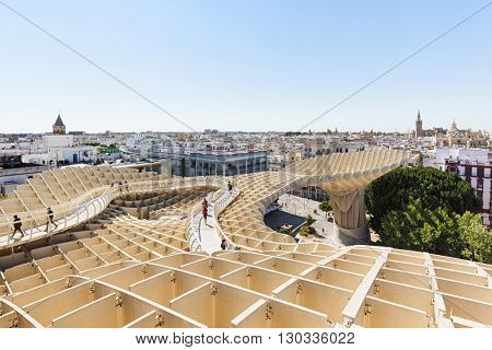 Seville, Spain - May 1, 2016: Seville cityscape seen from the upper platform of Metropol Parasol building, a wooden structure at Plaza de la Encarnacion. People walking around and enjoying the view.
