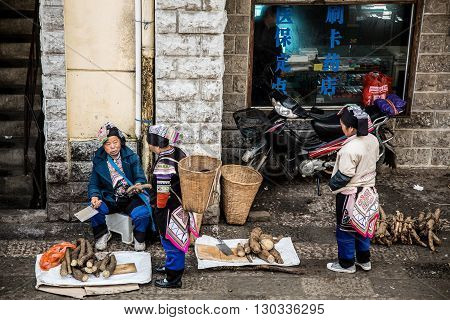 YUANYANG, CHINA - FEBRUARY 28,2016: Chinese Hani farmers sell their goods on the market,The Hani or Ho people are an ethnic group of Southeast Asia