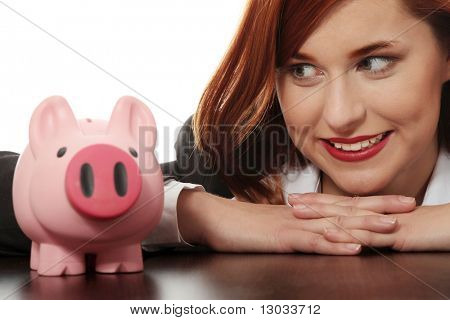 Young business woman looking on pink piggy bank, isolated on white background