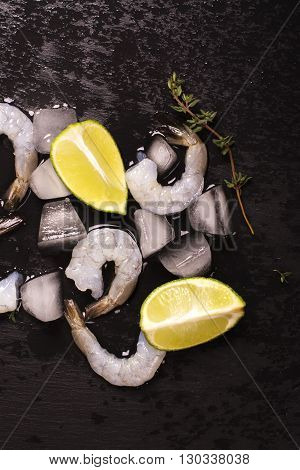 Raw prawns with lime and thyme over black wet stone background. Top view
