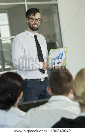 Young successful business man presenting the results of the latest project he has been workng on