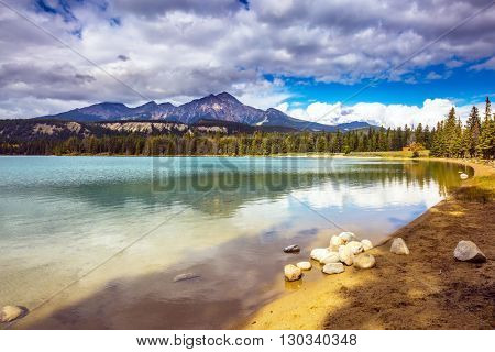 Pretty round lake in the coniferous forest. Canadian Rocky Mountains, Jasper National Park, lake Annette