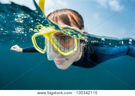 Close up underwater shot of the lady freediver in yellow mask
