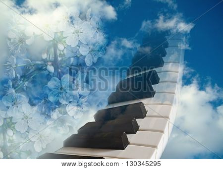 piano keyboard and flowers of cherry against the blue spring sky.The concept of spring mood.
