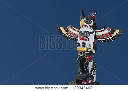 A Totem Wood Pole In The Blue Background