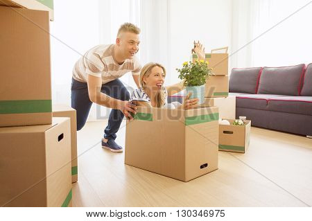 Funny couple having fun while moving into new apartment