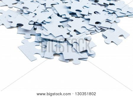 Pile of grey blank puzzle pieces isolated on white background