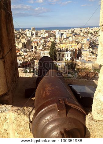 Cannon in the window of the Citadel. Architecture of Tripoli seen from the Citadel of Raymond de Saint-Gilles in Tripoli