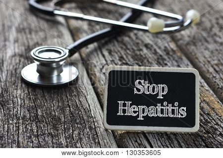 Medical Concept- Stop Hepatitis word written on blackboard with Stethoscope on wood background