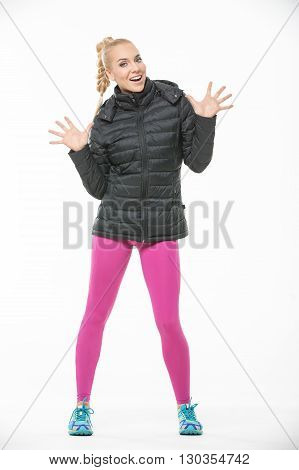 Sportive blonde girl in the sportswear stands on the white background in the studio. She wears cyan-yellow sneakers, pink pants and black jacket. She holds her hands raised with palms outward. She looks into the camera with a smile. Vertical.