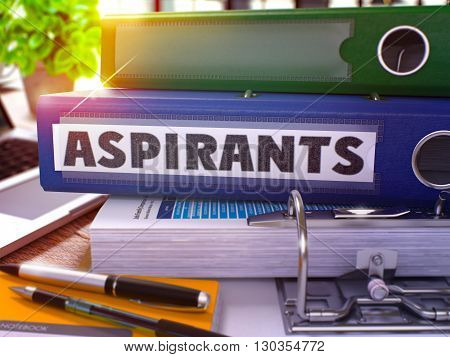Blue Ring Binder with Inscription Aspirants on Background of Working Table with Office Supplies and Laptop. Aspirants Business Concept on Blurred Background. 3D Render.