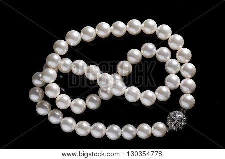 pearl necklace silver inlay clasp black background