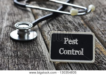 Medical Concept-Pest Control word written on blackboard with Stethoscope on wood background