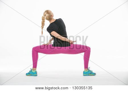 Pretty blonde gymnast in the sportswear squats with divorced feet on the white background in the studio. Shoot from the back. She wears cyan-yellow sneakers, pink pants and black t-shirt. Her right hand is on the left leg, her left hand is behind her back