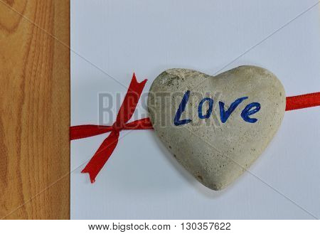 heart rock on white paper tie red ribbon