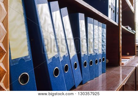 Brown Rack With Blue Folders In A Row Close-up