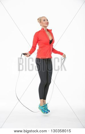 Pretty blonde girl in the sportswear jumps with skipping rope on the white background in the studio. She wears cyan-yellow sneakers, black pants, black t-shirt and red hoody. Her feet are off the floor. She looks up with a smile. Vertical.