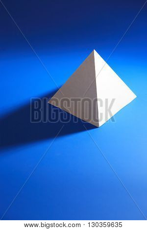 Geometry concept. One white paper pyramid on blue background