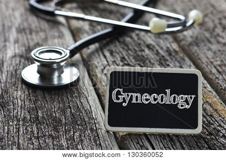 Medical Concept- Gynecology word written on blackboard with Stethoscope on wood background