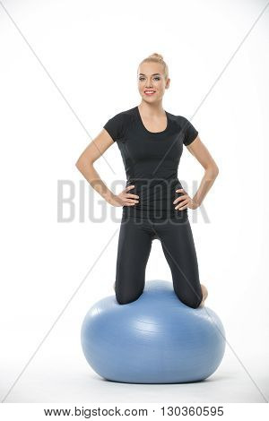 Cute blonde girl in the sportswear is on the blue fitball on the white background in the studio. She wears black pants and black t-shirt. Her hands are on her waist. She looks into the camera with a smile. Vertical.