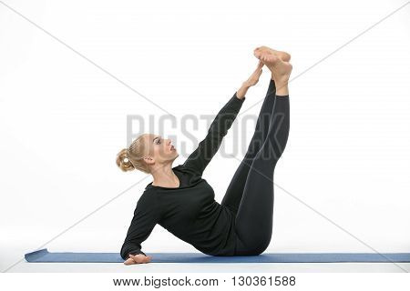 Sportive blonde girl in the sportswear does exercise barefoot on the white background in the studio. She wears black pants and black long sleeve t-shirt. She is on a blue gymnastic mat. She leans on the right elbow, legs are stretched up and the left hand