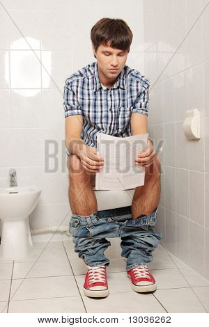 Young handsome man sitting on toilet and reading magazine.
