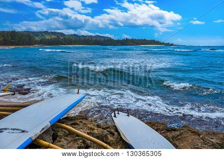 Surfboards by the sea with waves breaking on to shore
