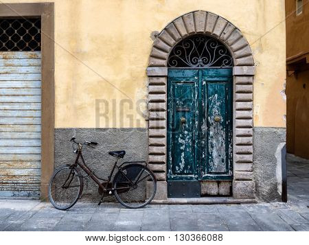 Fringed door and bike in Lucca Italy