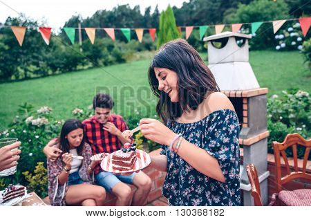 Portrait of young beautiful woman eating piece of cake and having fun in a outdoors summer barbecue with his friends