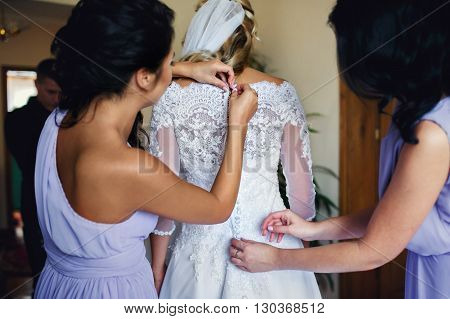 Bridesmaids Helping Beautiful Blonde Bride Get Ready For Wedding