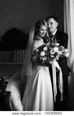Romantic Newlyweds Hugging In Hotel Near Window With Bouquet B&w