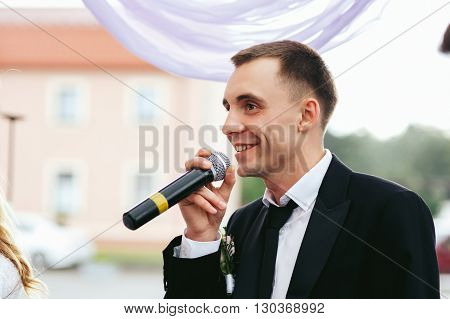 Handsome groom taking vows at wedding ceremony