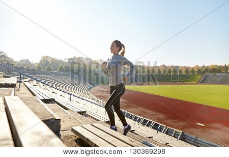 fitness, sport, exercising and people concept - happy young woman running upstairs on stadium