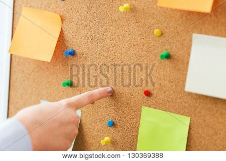 office, business, people and education concept - close up of hand pointing to to cork board with stickers and office pins