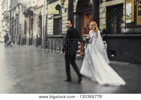 Romantic Newlyweds Walking Down Old European Street
