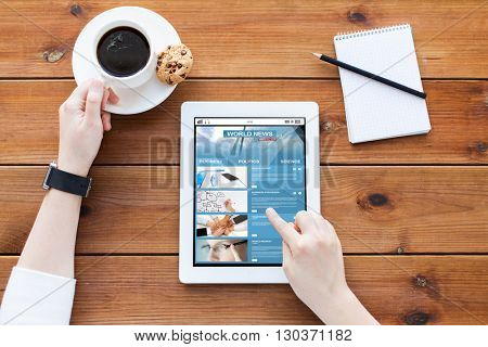 business, technology, mass media and people concept - close up of woman with business news on tablet pc computer screen, notebook and coffee on wooden table