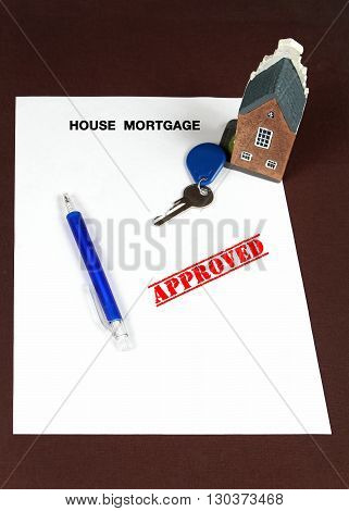 House mortgage approved concept with key on a paper