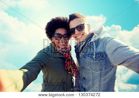 people, leisure and technology concept - happy international teenage couple taking selfie over blue sky and clouds background