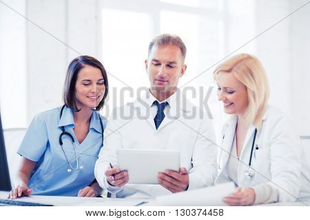 healthcare, medical and technology concept - doctors looking at tablet pc