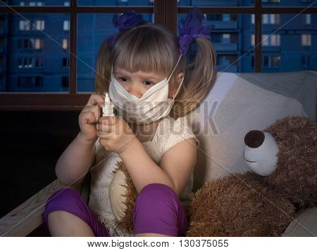 Little girl in medical mask holding a bottle with drops. On lap toy bear. The house, in the evening, the windows of houses, the city. Conceptually about diseases, infections and allergies