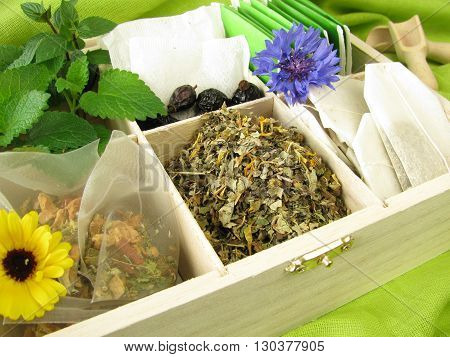 Tea box with loose tea, tea bags and fresh tea herbs